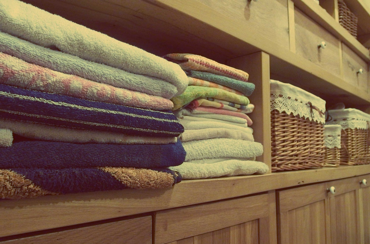 Laundry room baskets and hamper and neatly folded clothes and linens and towels