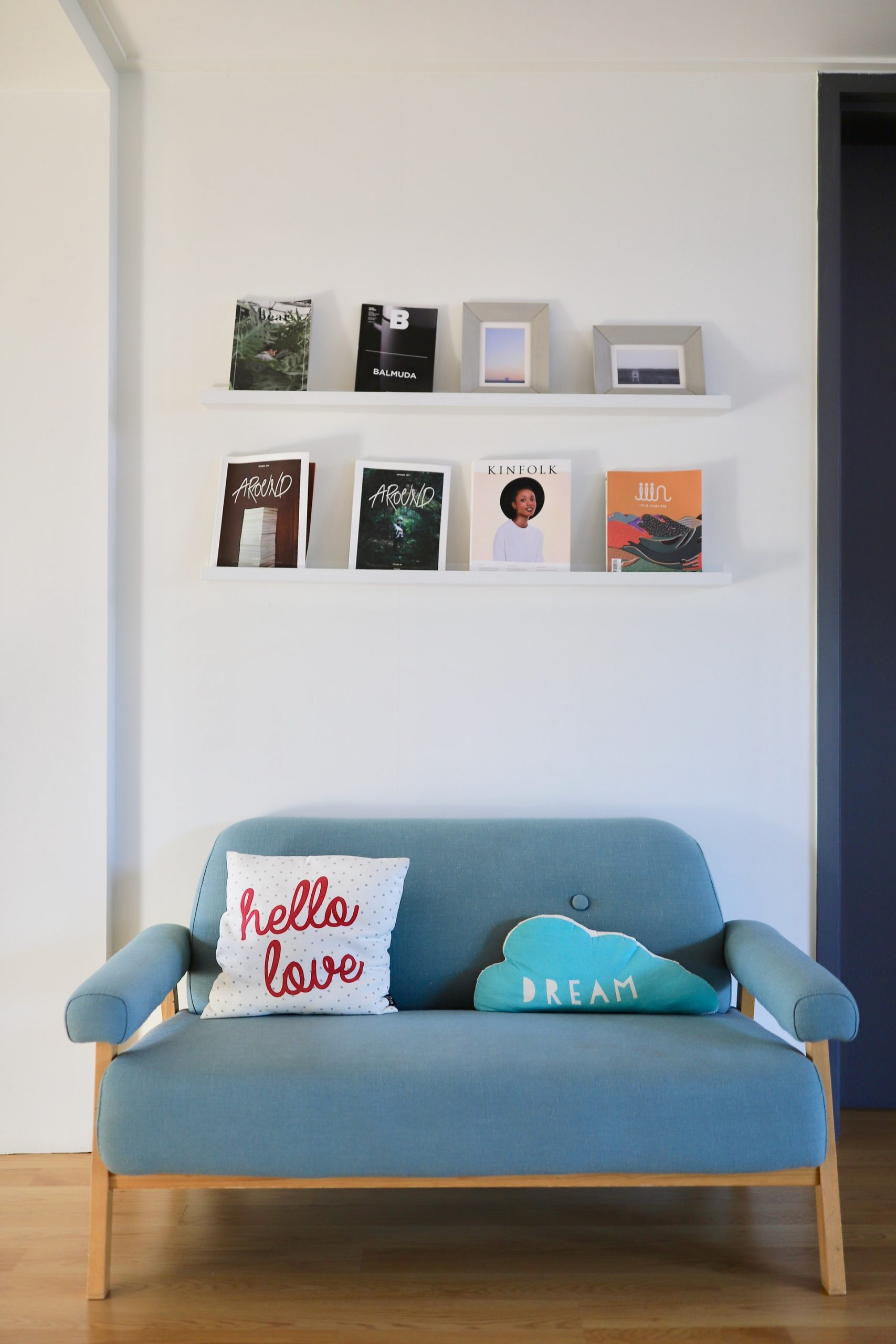 couch with cushions and display of personal items on shelves