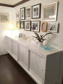 picture gallery art display over a credenza sideboard in living room